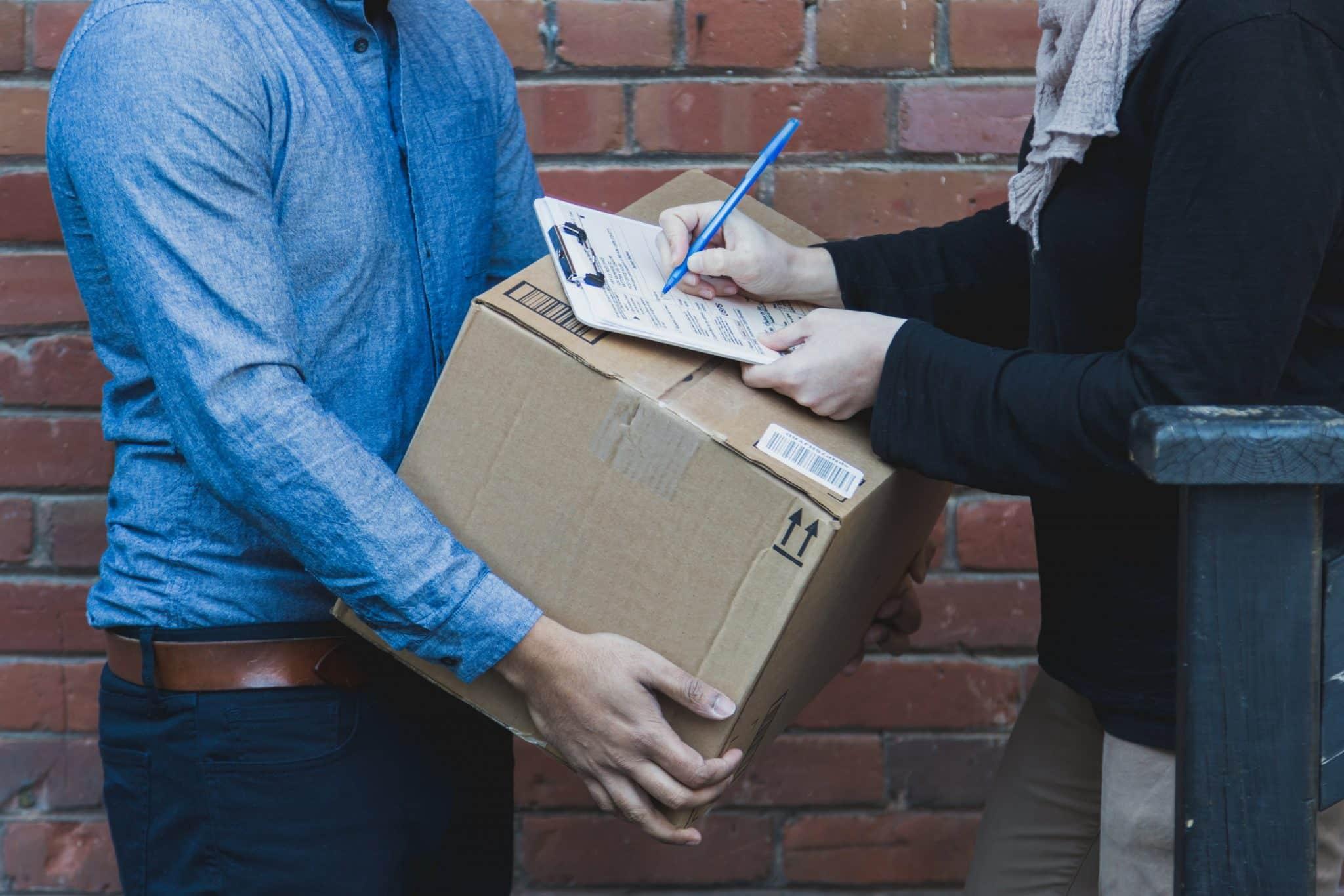 man-signing-for-shipping-box